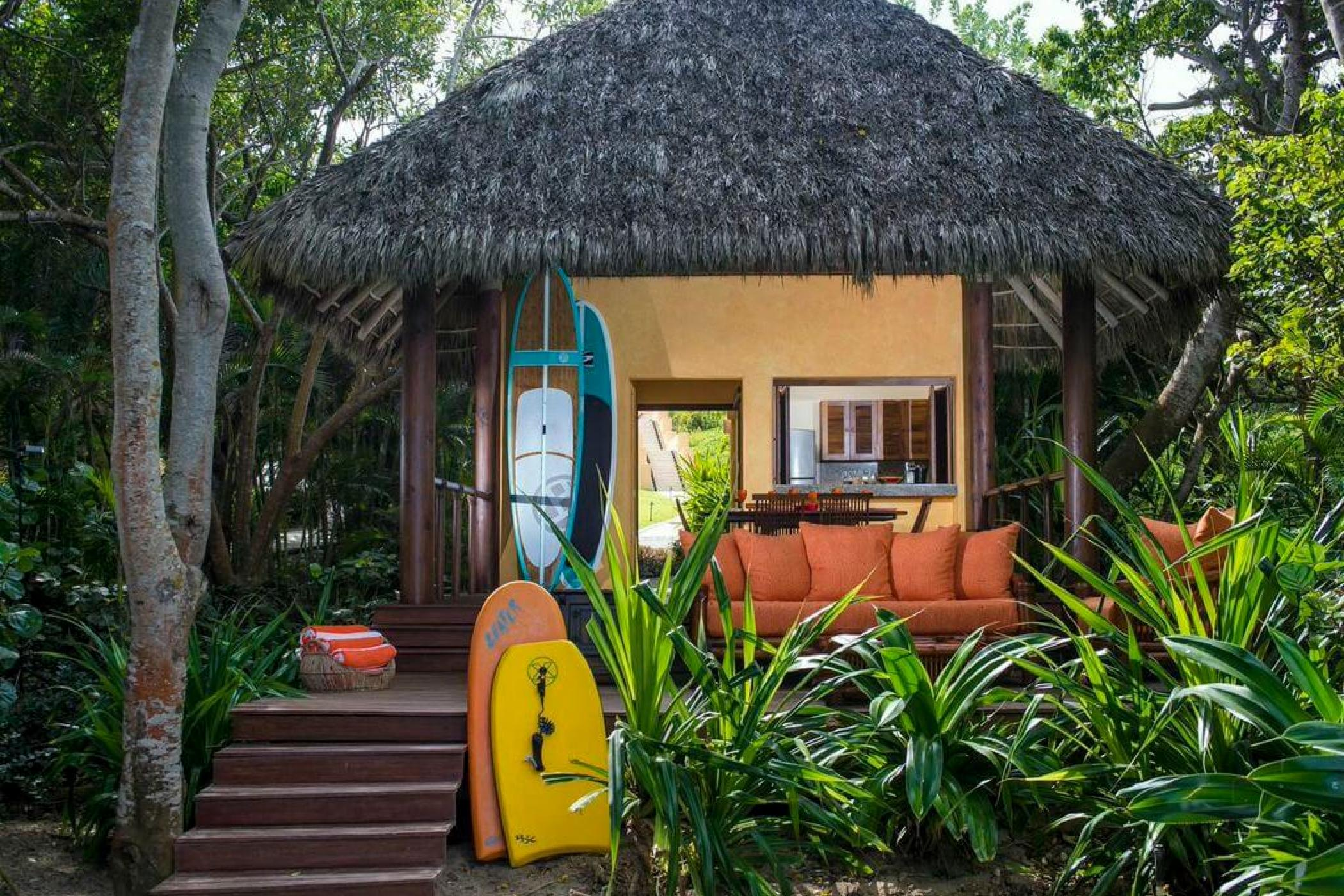 A private cabana on the beach comes stocked with paddle boards and other water toys.