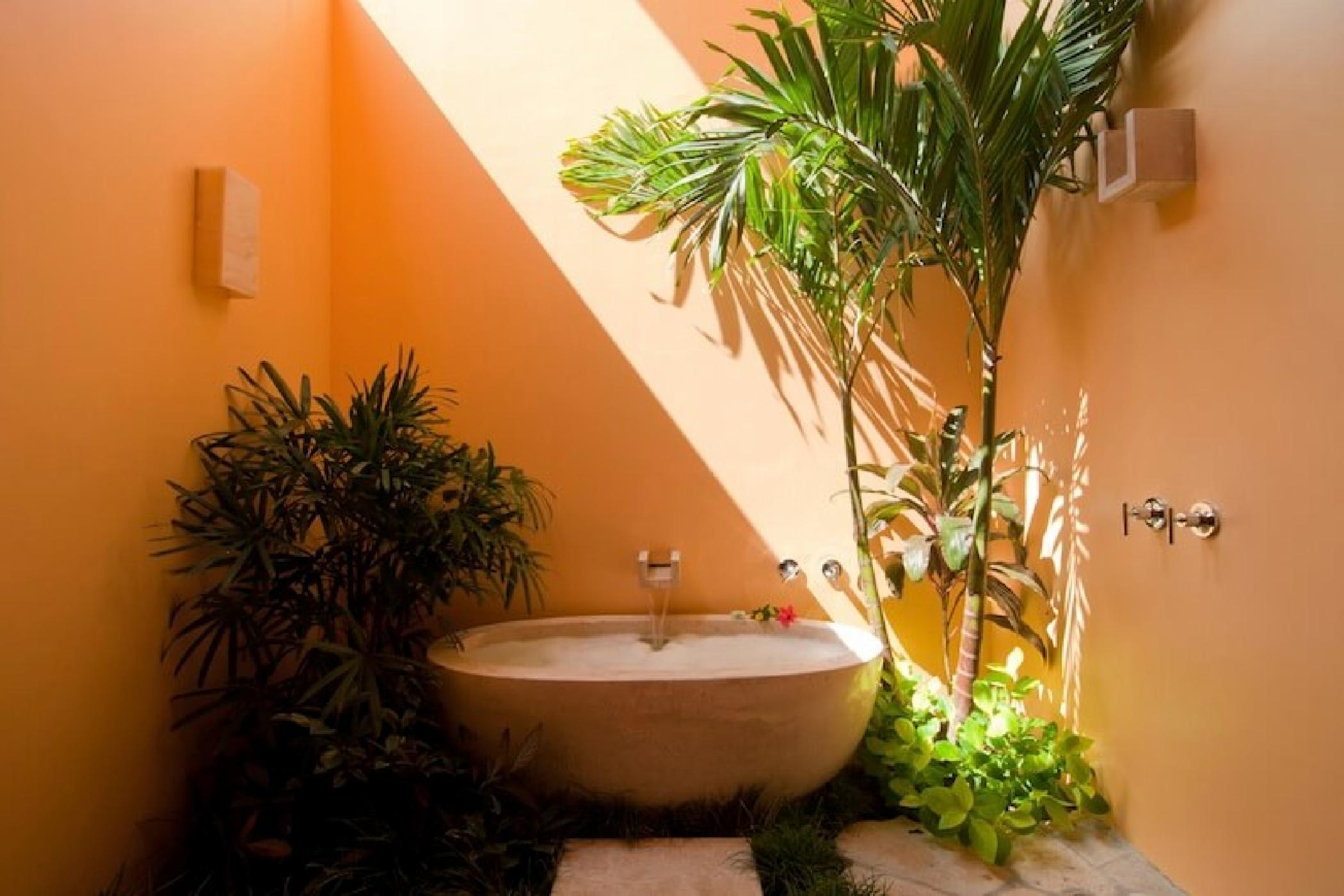 The turquoise master has an outdoor bathroom with a soaking tub.