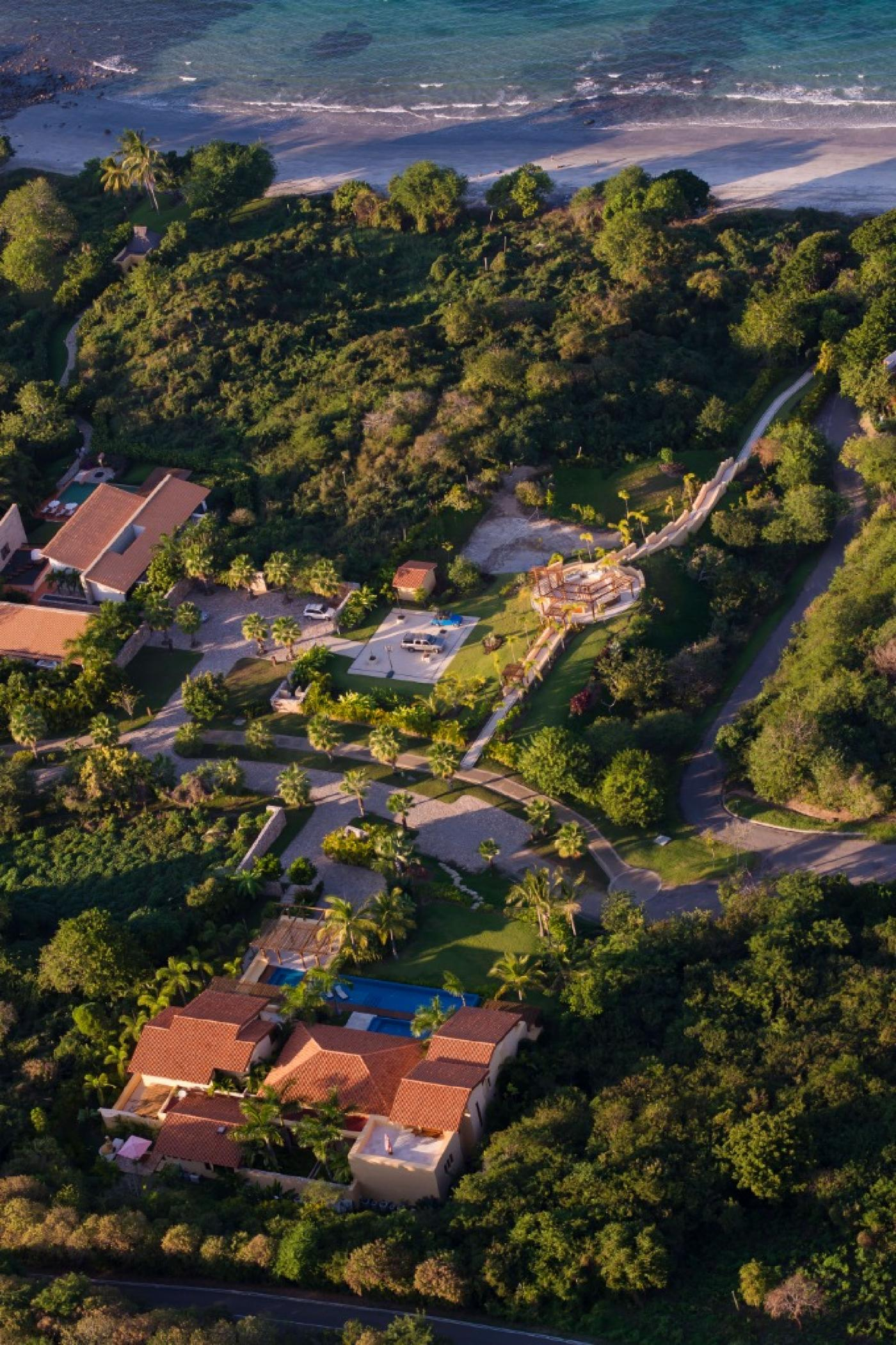 The unique property spills from the hillside through a garden, down to the beach.